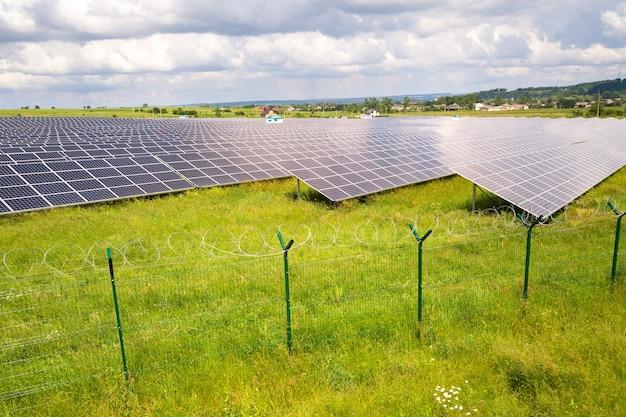 Luftaufnahme des solarkraftwerks auf der grünen wiese mit schutzdrahtzaun um sie herum. schalttafeln zur erzeugung sauberer ökologischer energie. Premium Fotos