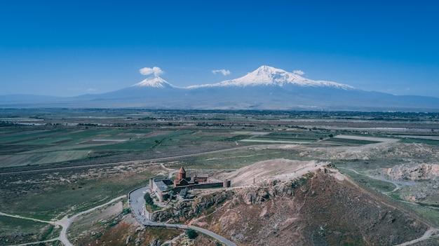 Luftaufnahme einer armenischen kirche auf einem hügel mit berg ararat und klarem blauem himmel Kostenlose Fotos