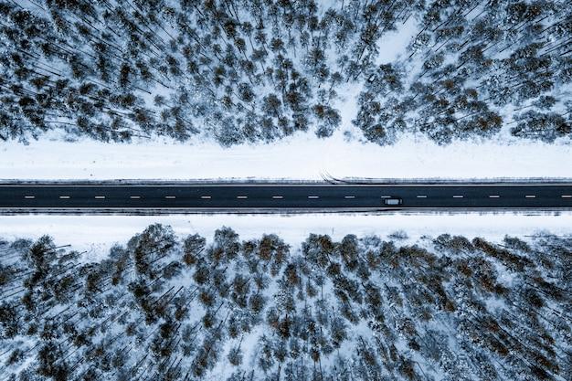 Luftaufnahme einer straße in einem wald, der im winter mit schnee bedeckt ist Kostenlose Fotos