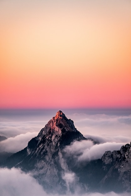 Luftaufnahme eines berges bedeckt im nebel unter dem schönen rosa himmel Kostenlose Fotos