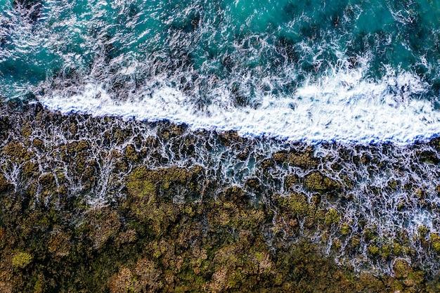 Luftaufnahme eines felsigen ufers mit schaumigen wellen Kostenlose Fotos