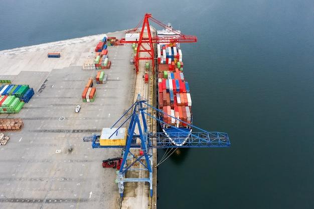 Luftaufnahme eines industriellen frachtschiffs mit containern zum laden in einem seehafen, von einer drohne geschossen Premium Fotos