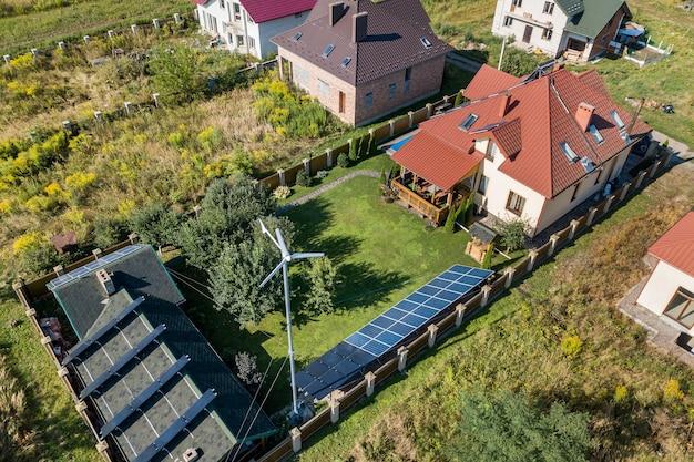 Luftaufnahme eines neuen autonomen hauses mit sonnenkollektoren, warmwasserbereitern auf dem dach und einer windbetriebenen turbine auf einem grünen hof. Premium Fotos