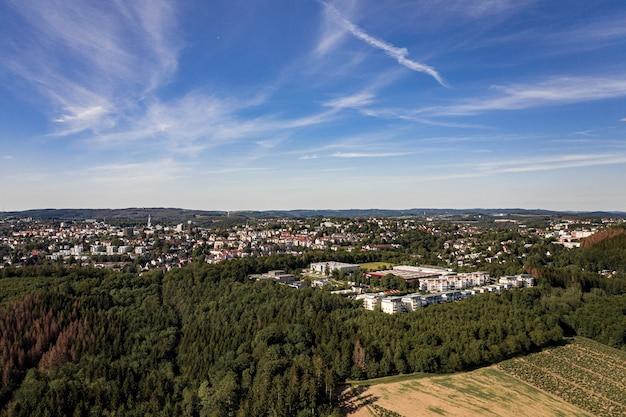Luftaufnahme eines stadtbildes in einer mit bäumen bedeckten landschaft Kostenlose Fotos