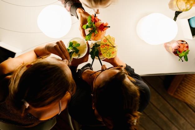 Luftaufnahme von drei frauen, die nachts zusammen cocktails mit einem strohhalm trinken Premium Fotos