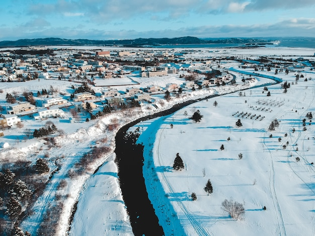 Luftaufnahme von häusern, feldern und bäumen, die mit schnee unter blauem und weißem himmel bedeckt sind Kostenlose Fotos