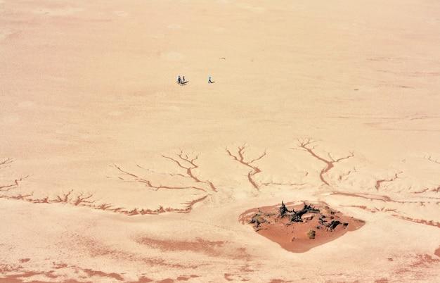Luftaufnahme von menschen, die tagsüber in der nähe des rissigen wüstenbodens stehen Kostenlose Fotos
