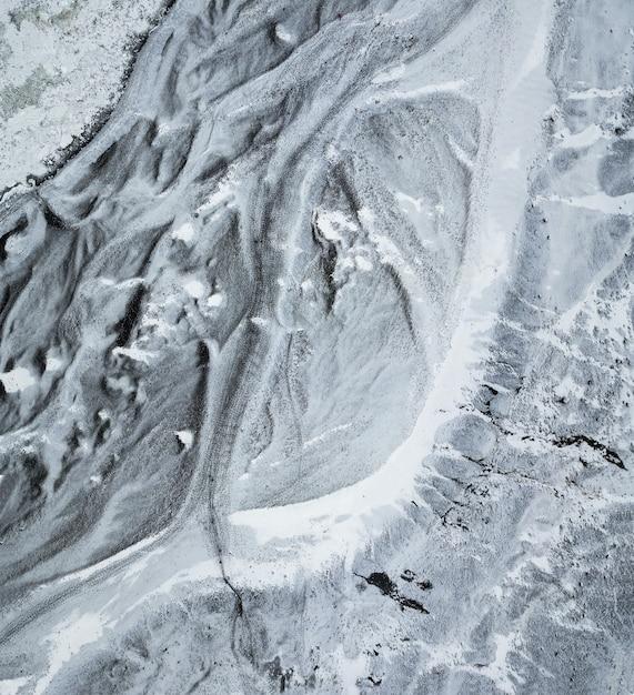 Luftaufnahme von oben nach unten auf dem eisigen pfad, der zum fuß des sólheimajökull-gletschers führt Kostenlose Fotos