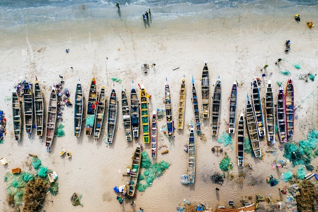 Luftaufnahme von verschiedenfarbigen booten an einem sandstrand mit dem meer in der nähe Kostenlose Fotos
