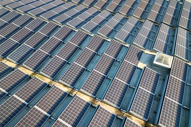 Luftaufnahme von vielen photovoltaik-sonnenkollektoren, die vom industriegebäudedach montiert werden. Premium Fotos