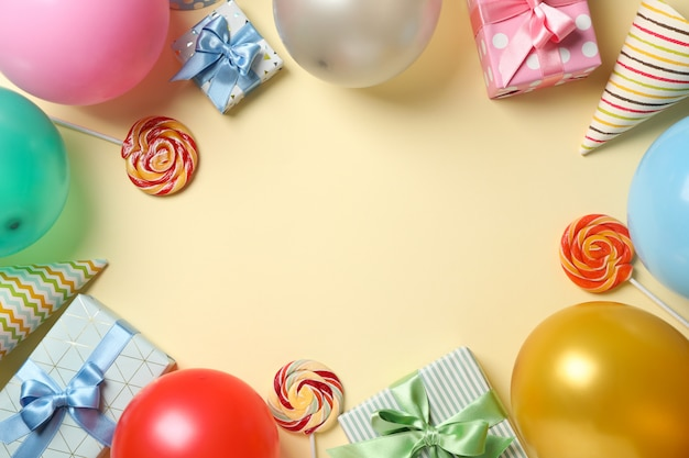 Luftballons, geschenkboxen, lutscher und geburtstagshüte auf farbigem hintergrund, platz für text Premium Fotos