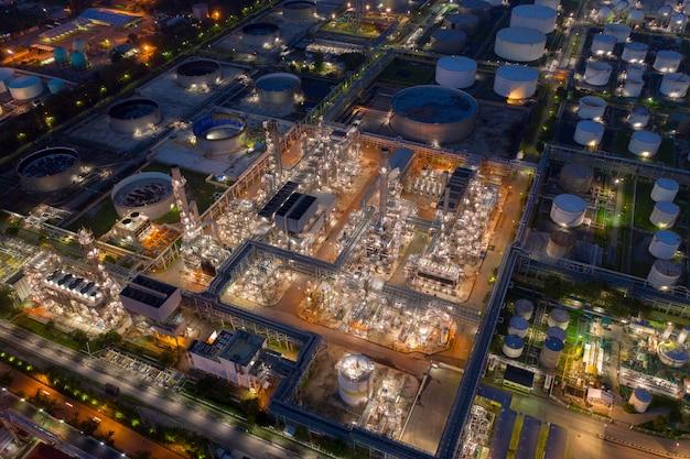 Luftbrummenansicht über enorme erdölraffineriefabrik nachts mit vielen sammelbehälter und destillationsturm. Premium Fotos