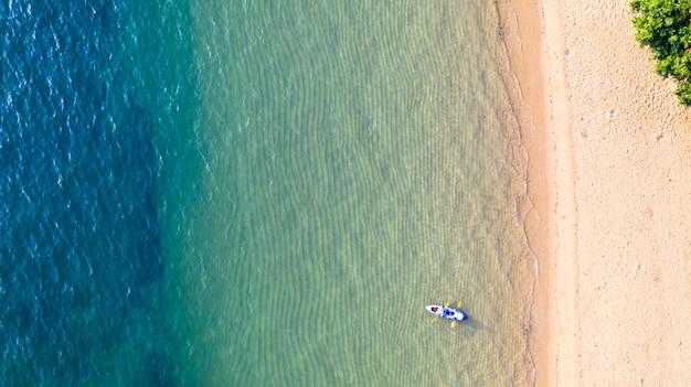 Luftdraufsicht des kayakfahrens um meer mit blauem smaragdwasser des schattens und wellenschaumhintergrund Premium Fotos