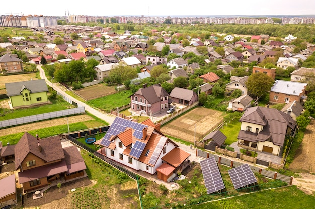 Luftdraufsicht des neuen modernen wohnhaushäuschens mit blauem glänzendem solarpaneelsystem des fotos voltaic auf dach. erneuerbare ökologische ökostrom-produktionskonzept. Premium Fotos