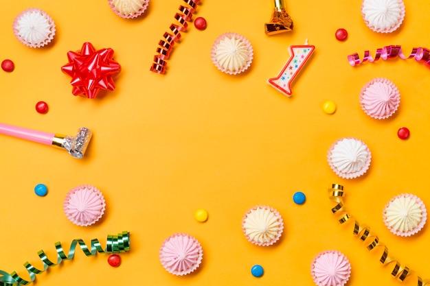 Luftschlangen; bandschleife; kerze nummer eins; edelsteine auf gelbem hintergrund Kostenlose Fotos
