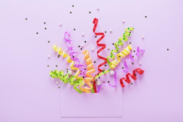 Luftschlangen und geöffneter umschlag auf violett Premium Fotos