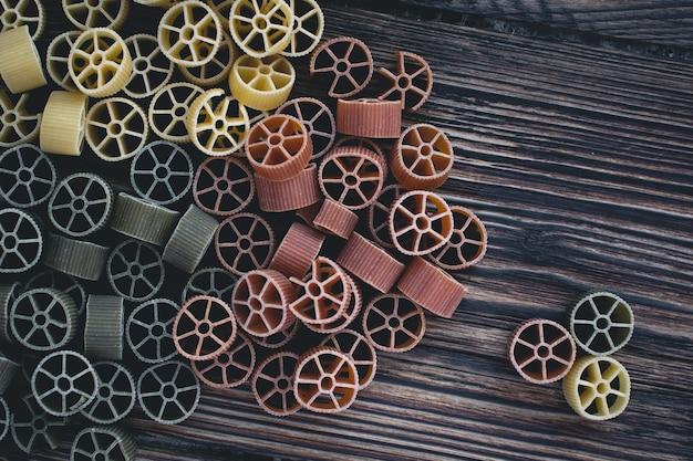 Luftschuß von bunten radteigwaren auf einem hölzernen hintergrund Kostenlose Fotos