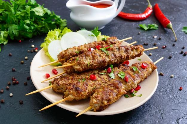 Lula kebab ist ein traditionelles arabisches gericht. fleischschaschlik auf holzspießen auf schwarzem hintergrund. Premium Fotos