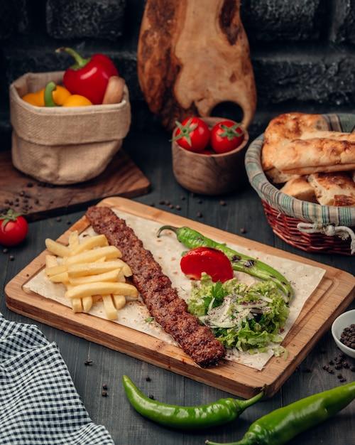 Lula kebab serviert mit pommes frites, salat und gegrilltem pfeffer Kostenlose Fotos
