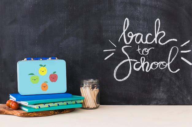 Lunchbox nahe notizbüchern und bleistiften Kostenlose Fotos