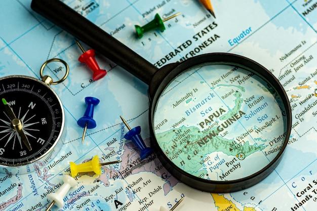 Lupe auf dem selektiven fokus der weltkarte an der papua-neu-guinea karte. - reise- und geschäftskonzept. Premium Fotos