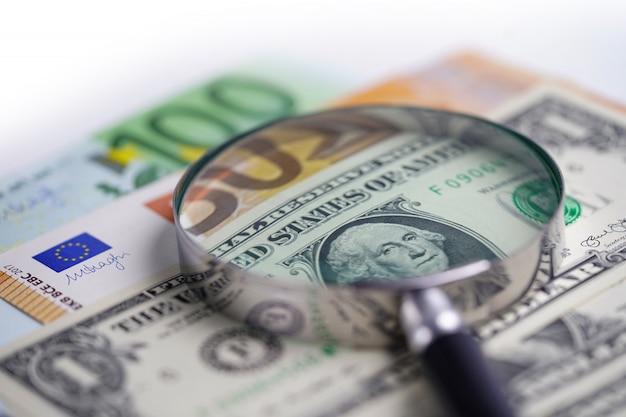 Lupe auf euro- und us-dollar-banknoten. Premium Fotos