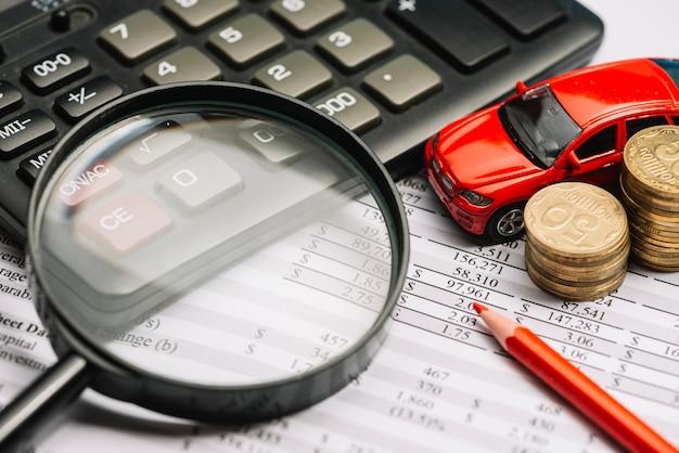Lupe über dem taschenrechner- und finanzbericht mit auto- und münzenstapel Kostenlose Fotos