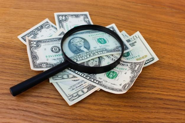 Lupe und dollar auf dem tisch Premium Fotos
