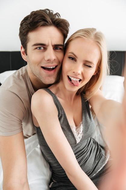 Lustige attraktive liebhaber, die morgens selfie machen und gesicht verziehen Kostenlose Fotos