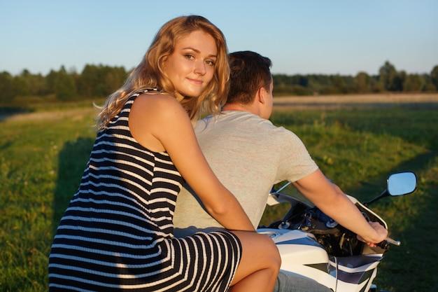 Lustige fahrt. junges paar, das motorrad fährt. hübscher kerl und hübsche frau auf dem motorrad. junge reiter genießen sich auf der reise Premium Fotos