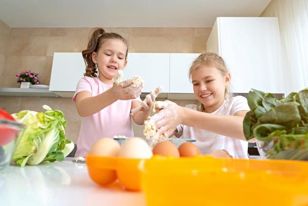 Lustige familienkinder bereiten den teig vor, backen kekse in der küche. schwestern haben spaß zusammen zu lachen Premium Fotos