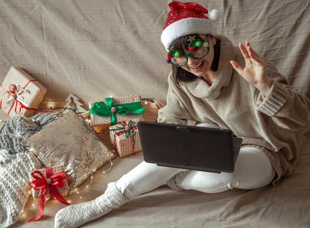 Lustige frau in der weihnachtsbrille und im weihnachtsmannhut sitzt an einem laptop Premium Fotos