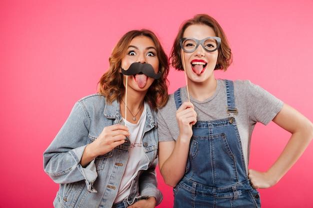 Lustige freundinnen, die gefälschten schnurrbart und gläser halten. Kostenlose Fotos