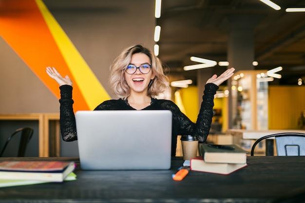 Lustige glückliche aufgeregte junge hübsche frau, die am tisch im schwarzen hemd sitzt und am laptop im mitarbeitenden büro arbeitet und brille trägt Kostenlose Fotos