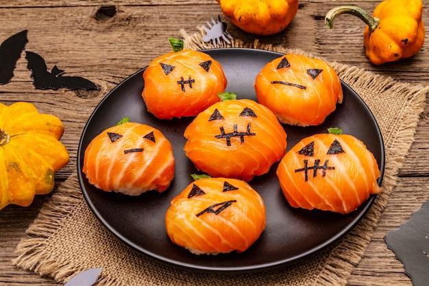 Lustige halloween-sushi-kürbis-kürbislaterne, sushi-monster. temari-sushi, sushi-bälle. gesundes essen für kinder Premium Fotos
