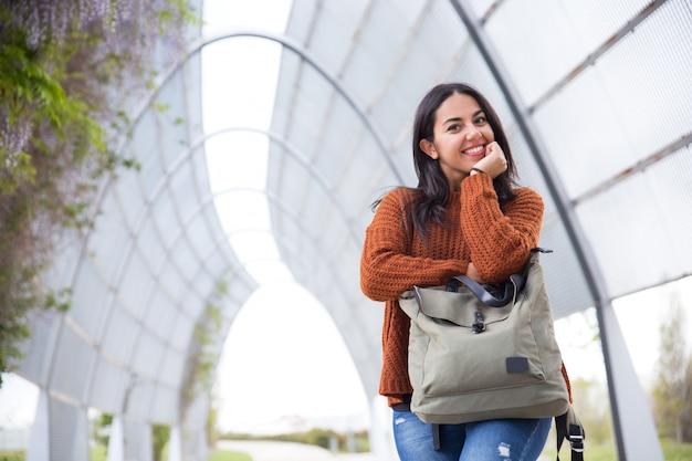 Lustige junge frau, die auf handtasche im stadtpark sich lehnt Kostenlose Fotos