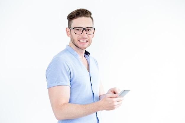 lustige junge mann mit smartphone pressen zähne