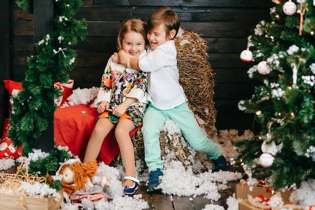 Lustige kinder, die im studio mit dekorationen des weihnachtsbaums und des neuen jahres umarmen. Premium Fotos