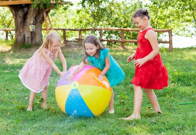 Lustige kleine mädchen freands, die mit einem wasserball im sonnigen garten spielen. Premium Fotos