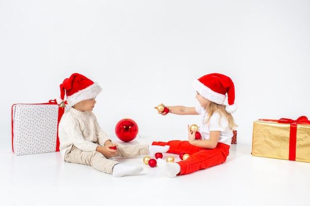 Lustige kleinkinder in sankt-hut, der zwischen geschenkboxen sitzt und mit weihnachtsbällen spielt. isoliert auf weißem hintergrund neujahr Premium Fotos
