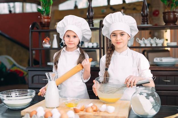 Lustige mädchen bereiten den teig in der küche zu. Premium Fotos