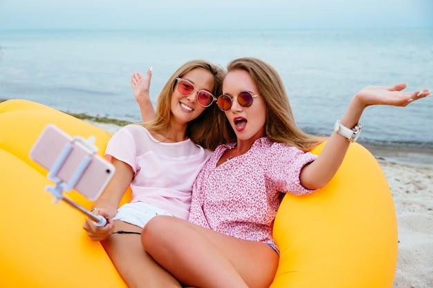 Lustige mädchen, die an der kamera beim nehmen eines selfie auf dem smartphone, sitzend auf luftsofa lamzac aufwerfen Kostenlose Fotos