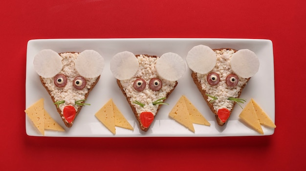 Lustige sandwiches für kinder formten niedliche mäuse mit käse, eiern und krabbenstangen auf rotem hintergrund, kunstkunstidee, draufsicht Premium Fotos