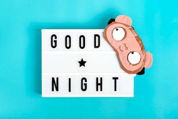 Lustige schlafmaske und leuchtkasten mit zitat gute nacht auf blauem hintergrund Premium Fotos
