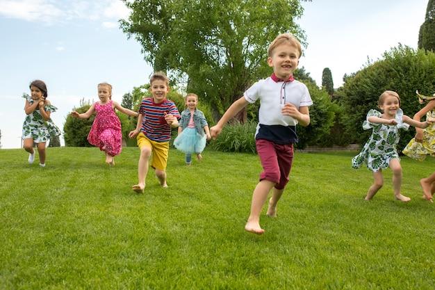 Lustige starts. kindermode-konzept. die gruppe von jugendlichen jungen und mädchen, die im park laufen. Kostenlose Fotos