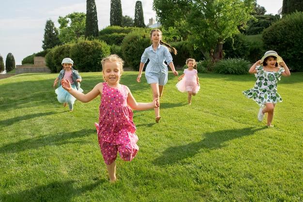 Lustige starts. kindermode-konzept. gruppe von jugendlichen jungen und mädchen, die am park laufen. kinder bunte kleidung, lebensstil, trendige farbkonzepte. Kostenlose Fotos