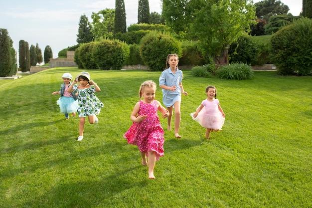 Lustige starts. kindermode-konzept. gruppe von jugendlichen jungen und mädchen, die am park laufen Kostenlose Fotos