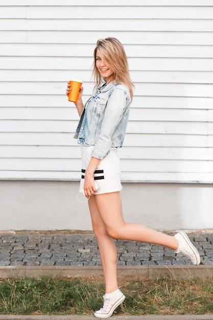 Lustige stilvolle junge frau im trendigen sportkleid in blauer jeansjacke in weißen turnschuhen mit einer orangefarbenen tasse mit einem cocktail, der spaß im freien nahe der holzwand hat. charmantes mädchen, das sich ausruht. Premium Fotos