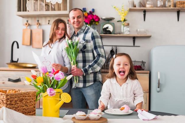 Lustige tochter, die kleinen kuchen nahe eltern mit grußkarte macht Kostenlose Fotos