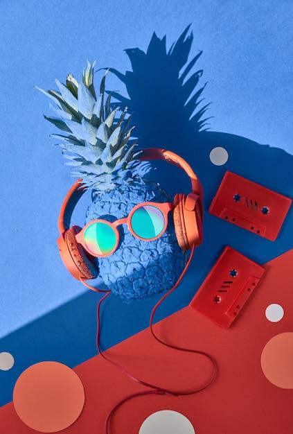 Lustige türkisfarbene ananas in sonnenbrille und kopfhörern mit einem schatten auf blauem und rotem papier Premium Fotos